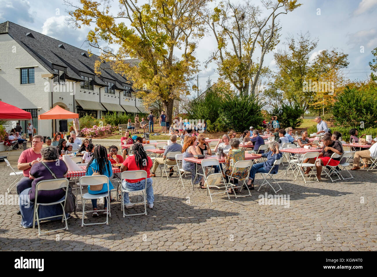 People,friends and neighbors, sitting enjoying a local food truck festival, eating their food and enjoying the lifestyle - Stock Image