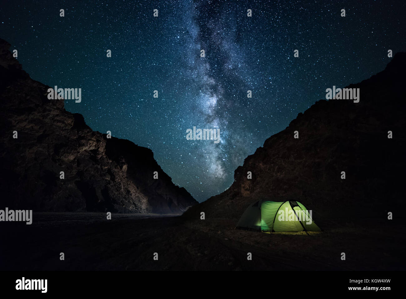 night rocky ravine, starry sky with bright milky way. a little camping - Stock Image