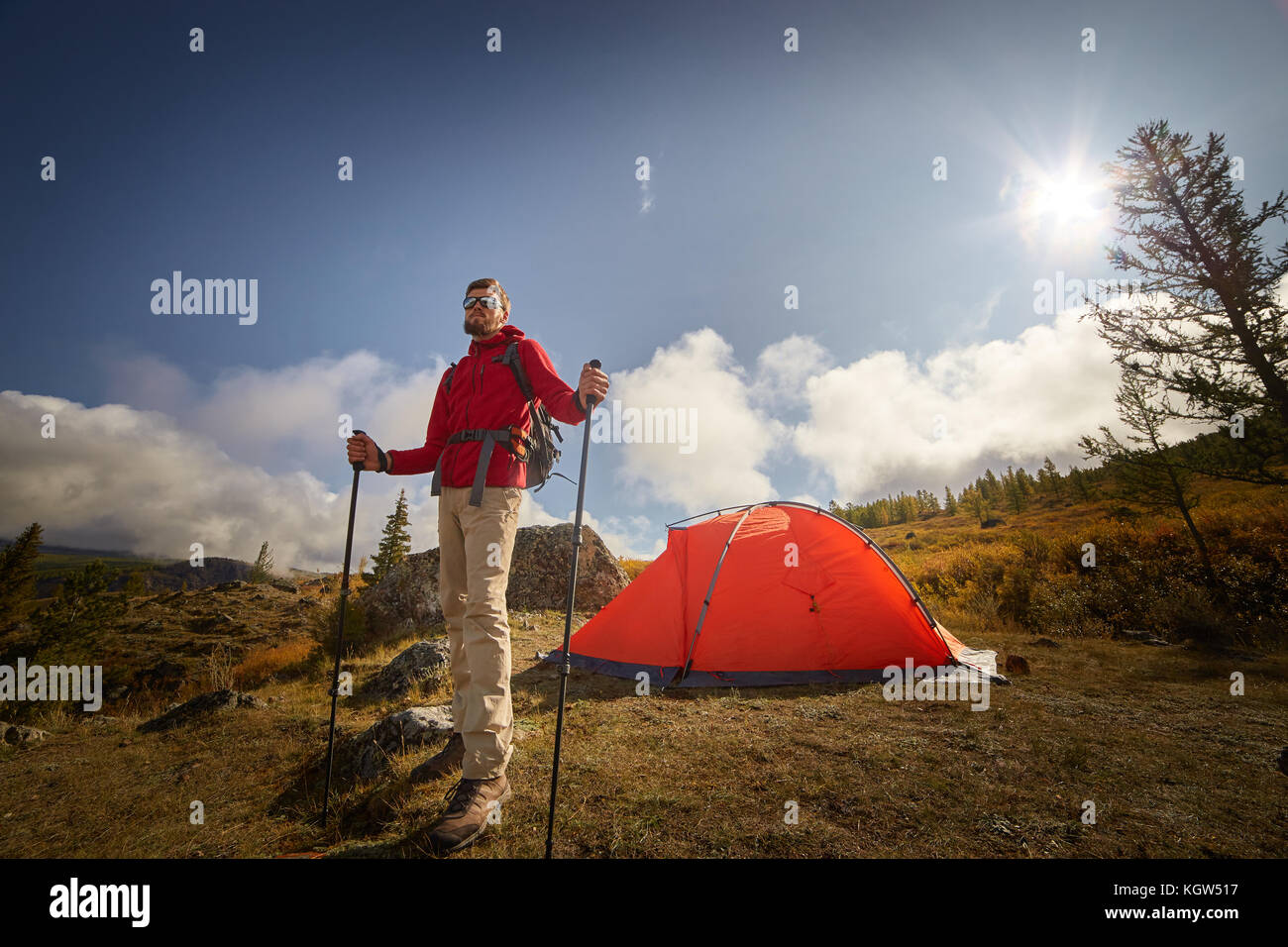 Backpacker with poles in hand. - Stock Image