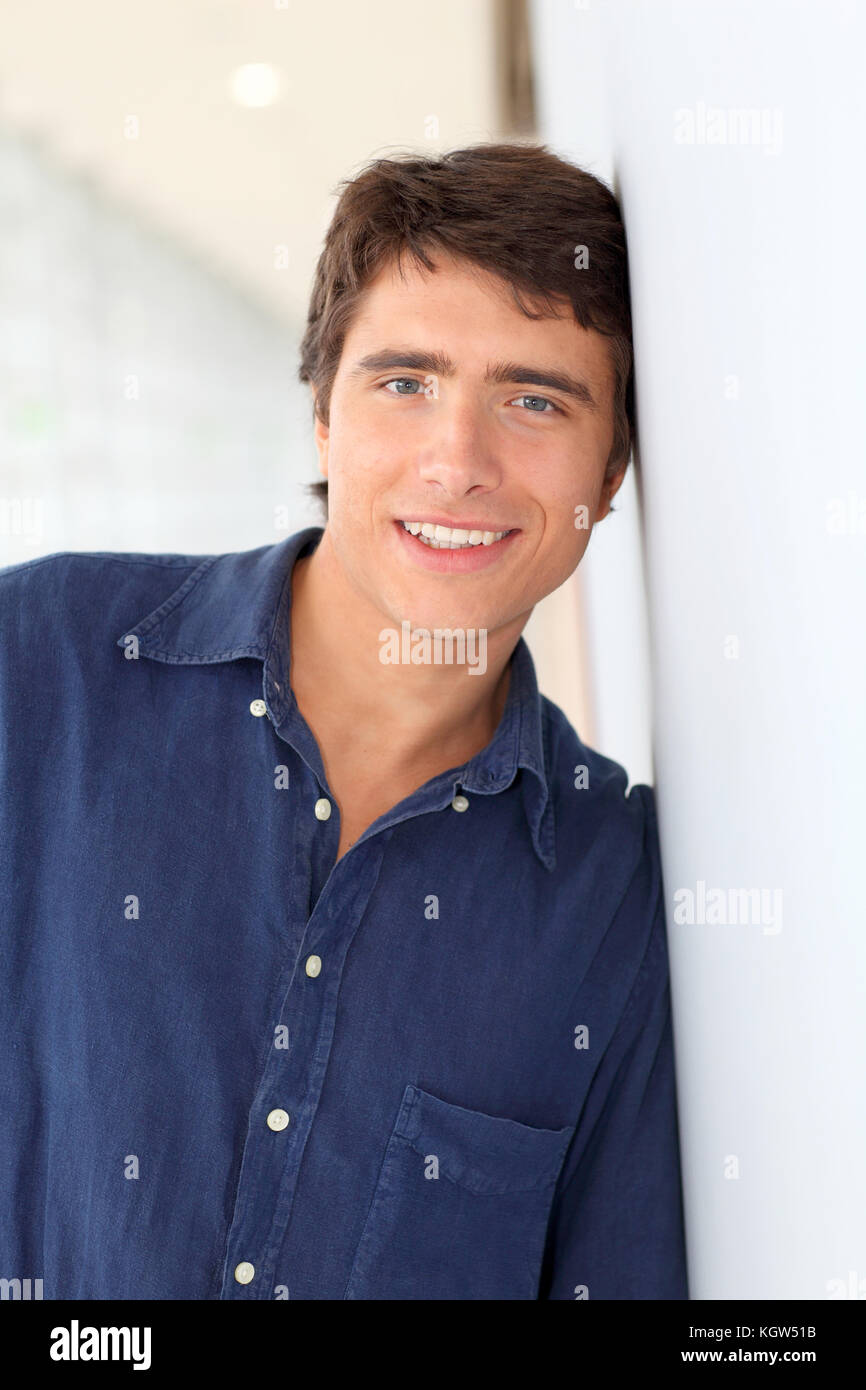 Portrait of young man standing on white background - Stock Image