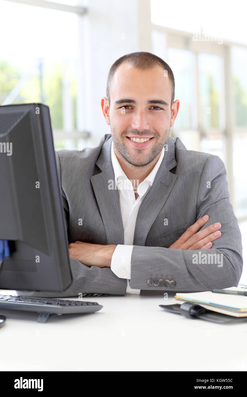 Portrait of satisfied businessman in office - Stock Image