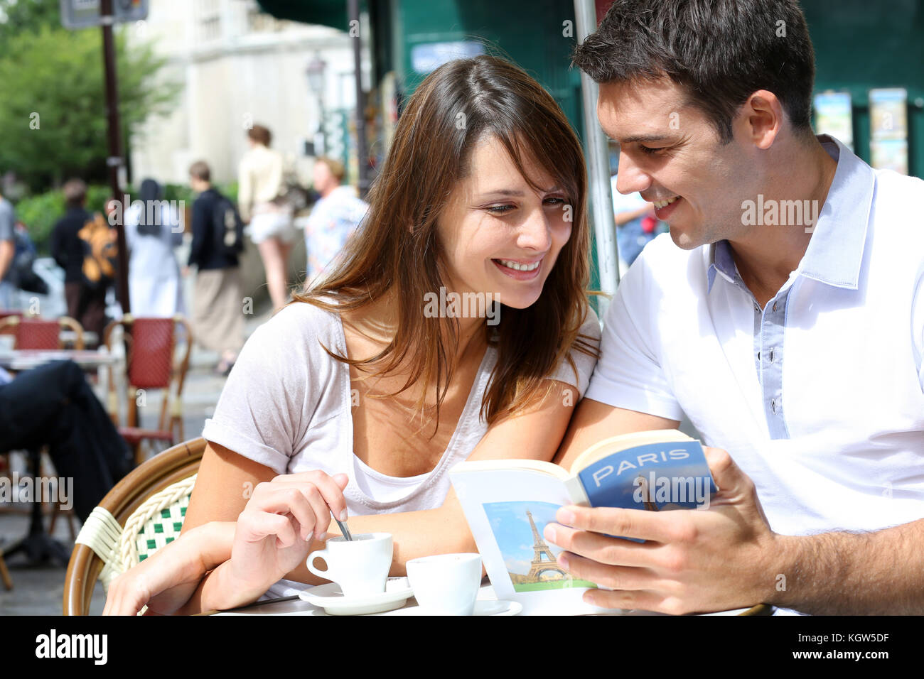 Couple on a coffee shop terrace reading tourist book - Stock Image