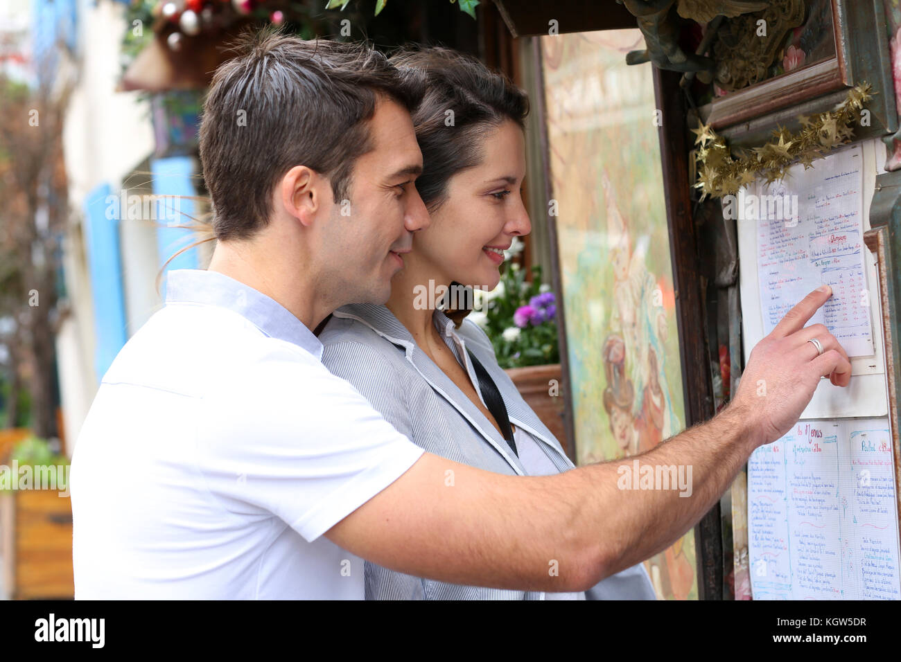 Couple in Paris looking at restaurant menu - Stock Image