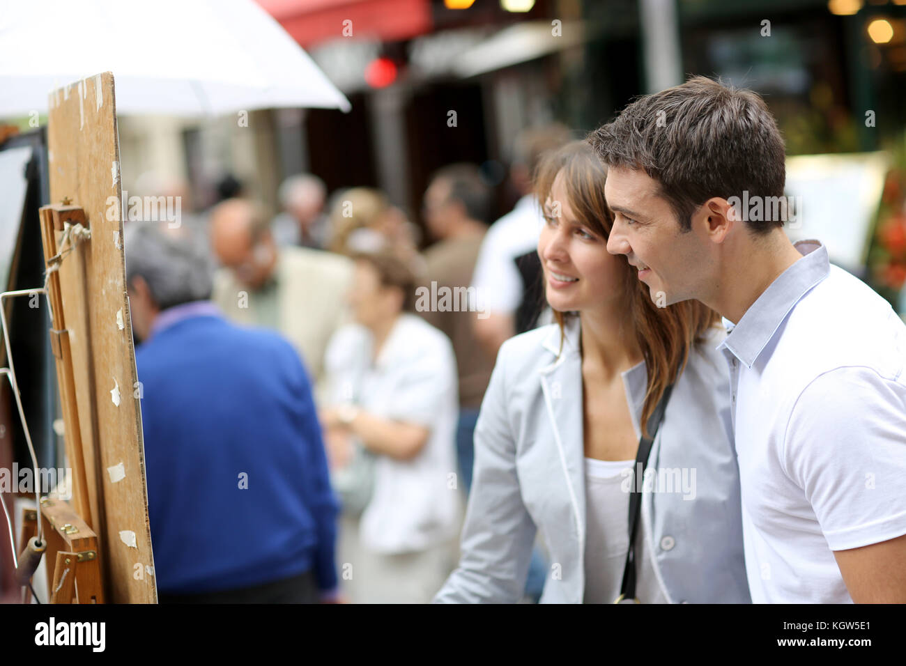 Couple in Paris looking at paintings in the street - Stock Image