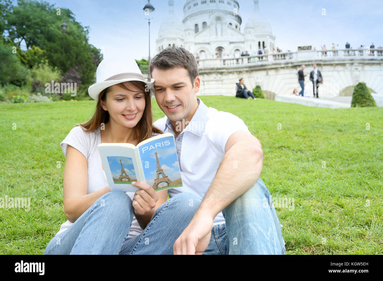 Couple in Paris sitting in front of Sacre Coeur Basilica - Stock Image
