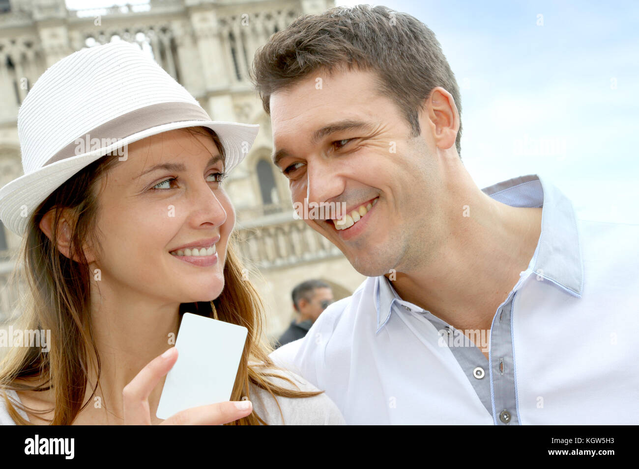 Couple showing tourist pass in front of Notre Dame - Stock Image