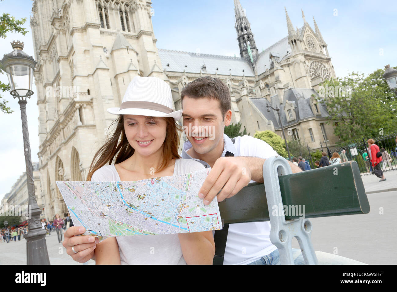 Tourist sitting in front of Notre Dame of Paris Cathedral - Stock Image