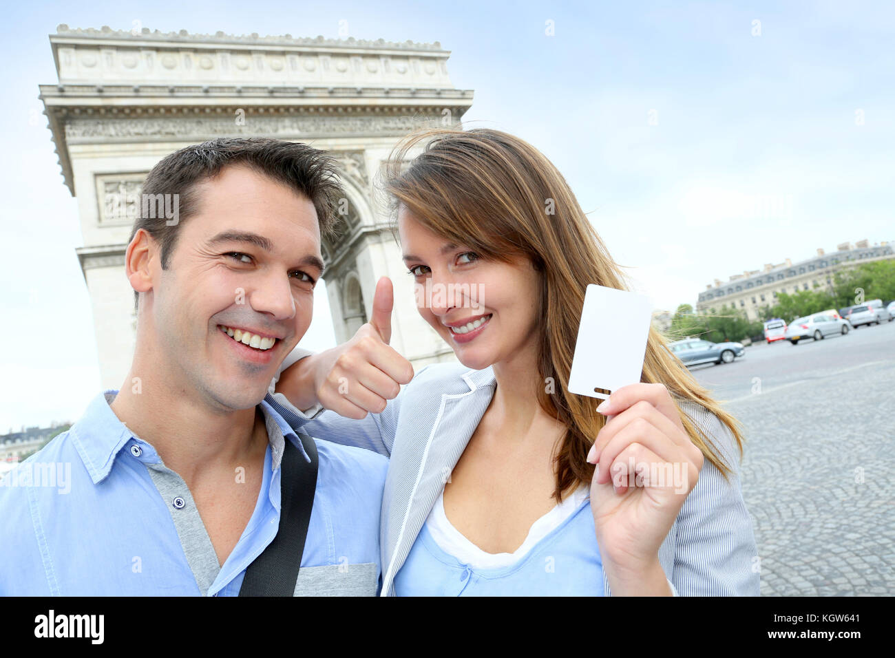 Cheerful couple holding tourist ticket by the Arch of Triumph - Stock Image