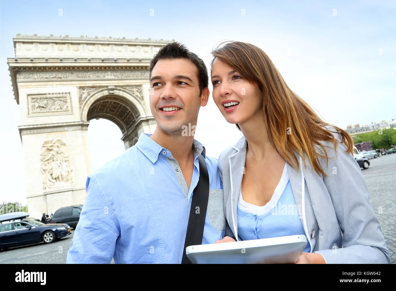Couple using tablet by the Arch of Triumph - Stock Image