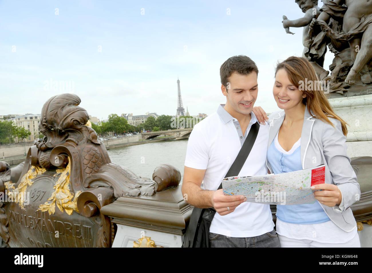 Couple reading tourist map on the Bridge Alexander the Third - Stock Image