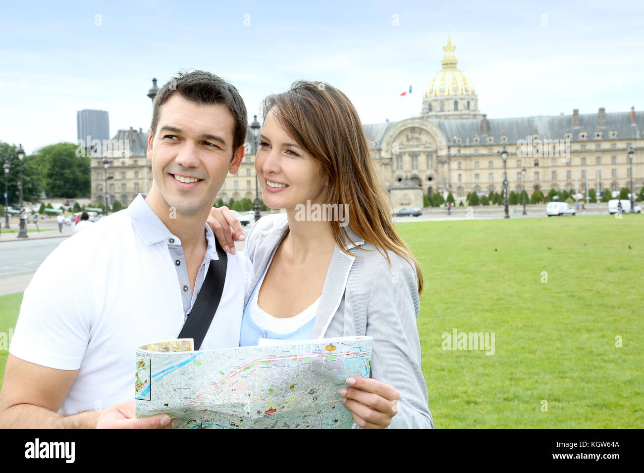 Couple reading tourist map in front of the Invalides building - Stock Image