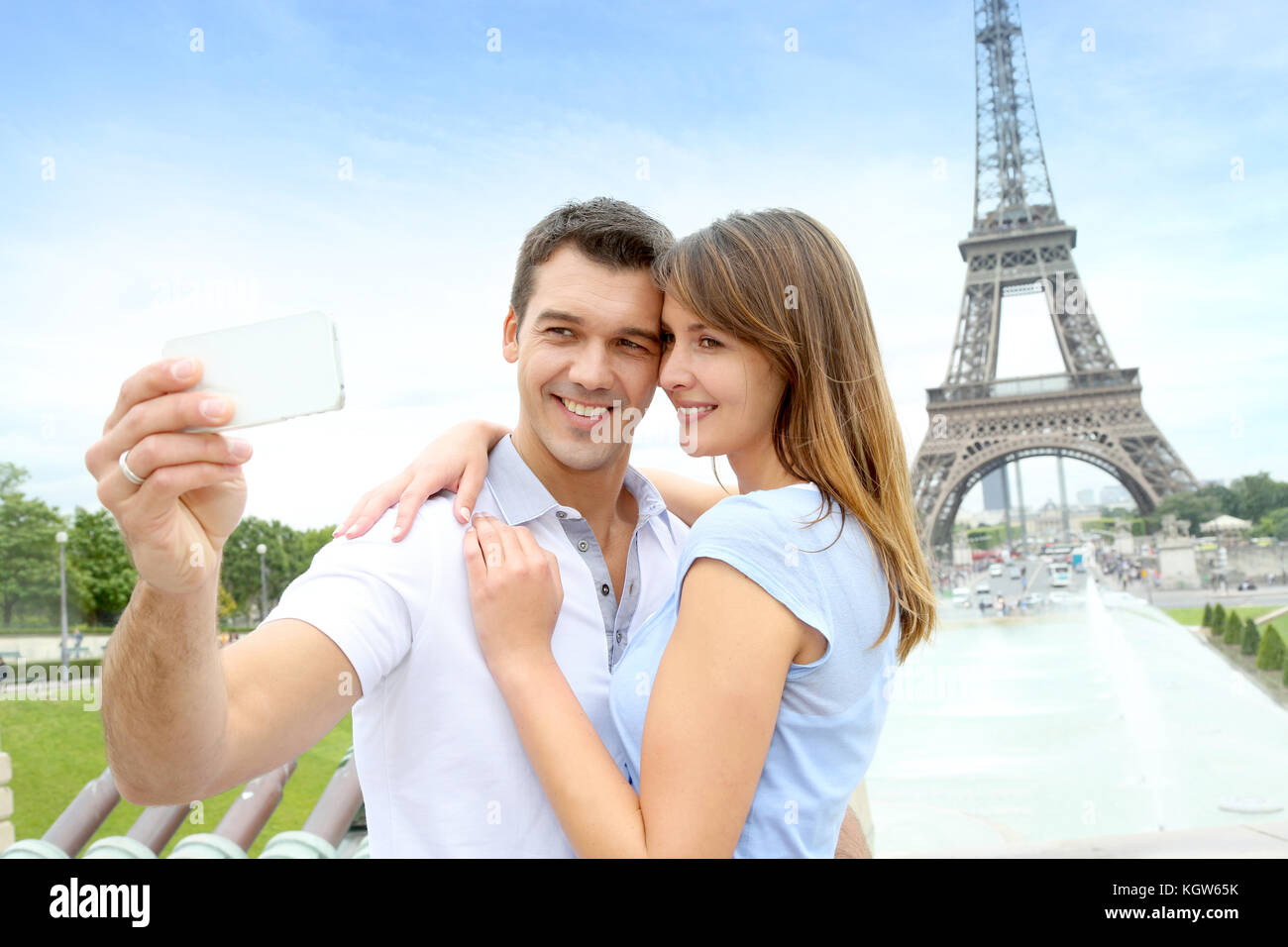 Couple in Paris taking pictures in front of Eiffel Tower - Stock Image