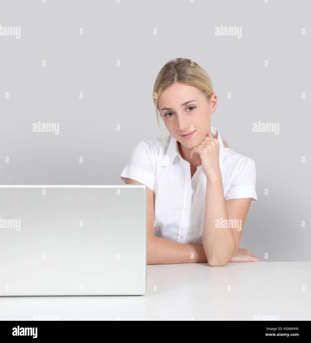 Portrait of woman sitting by laptop computer - Stock Image