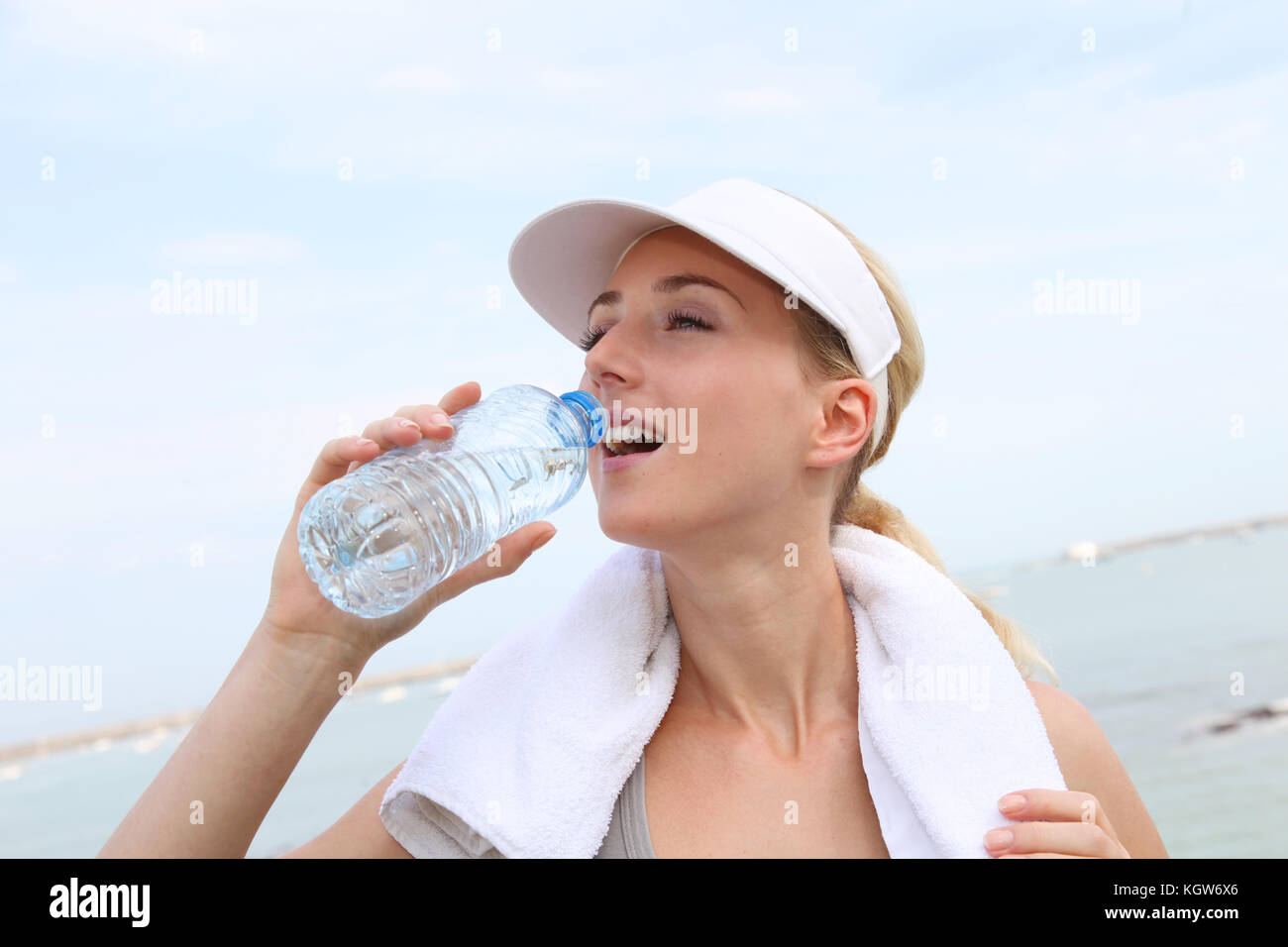 Portrait of jogger drinking water - Stock Image