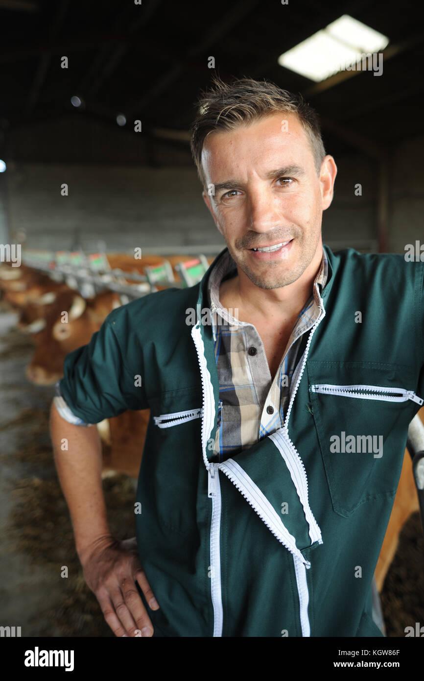 Portrait of smiling breeder in barn - Stock Image