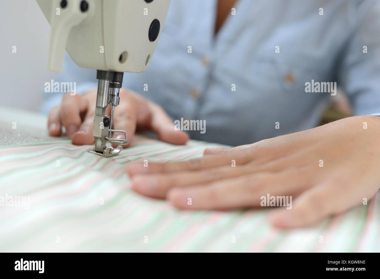Closeup on dressmaker hand using sewing machine - Stock Image