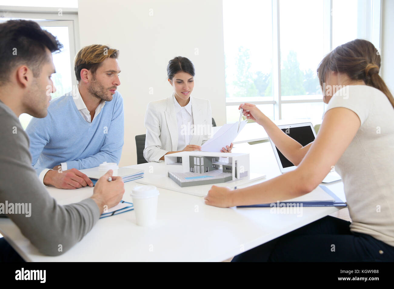 Team of architects meeting around table to talk about project - Stock Image