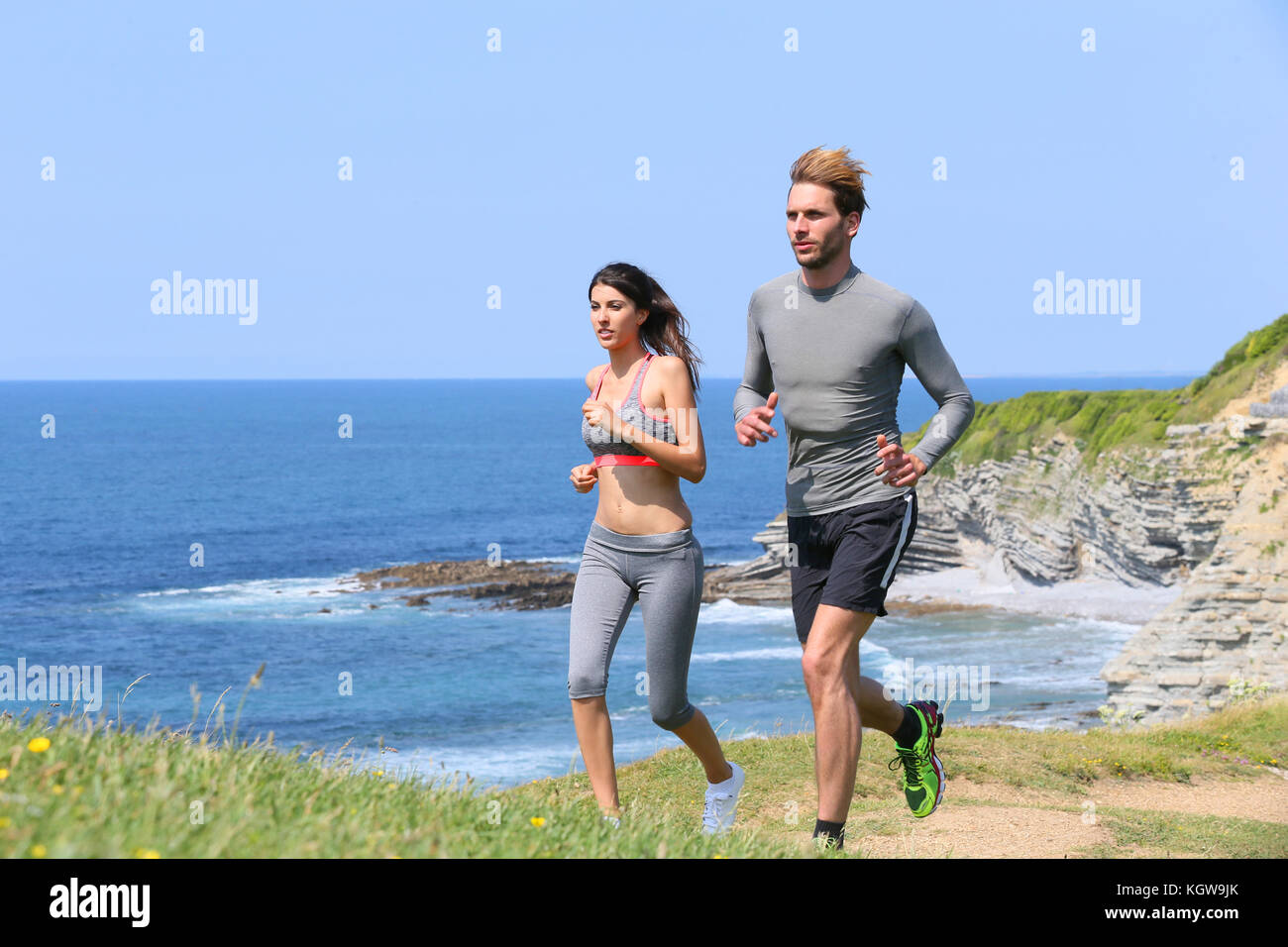 Couple of runners exercising by cliff - Stock Image