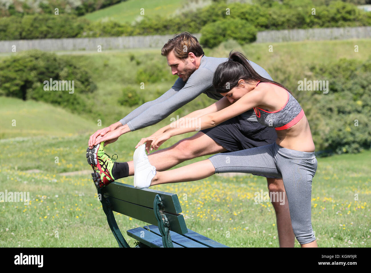 Couple of runners stretching out after running session - Stock Image