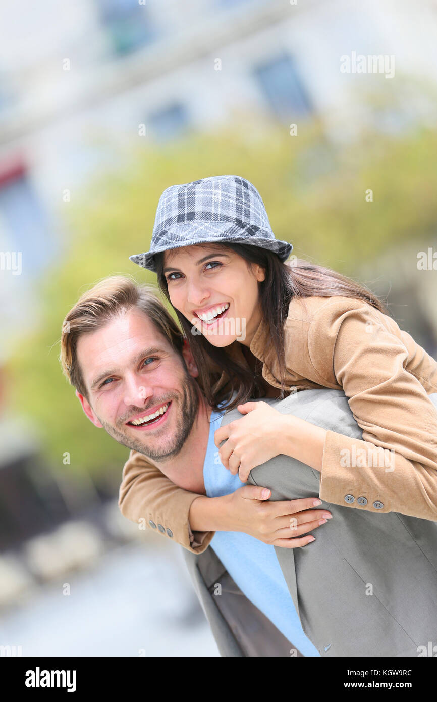 Young man giving piggyback ride to girlfriend in town - Stock Image