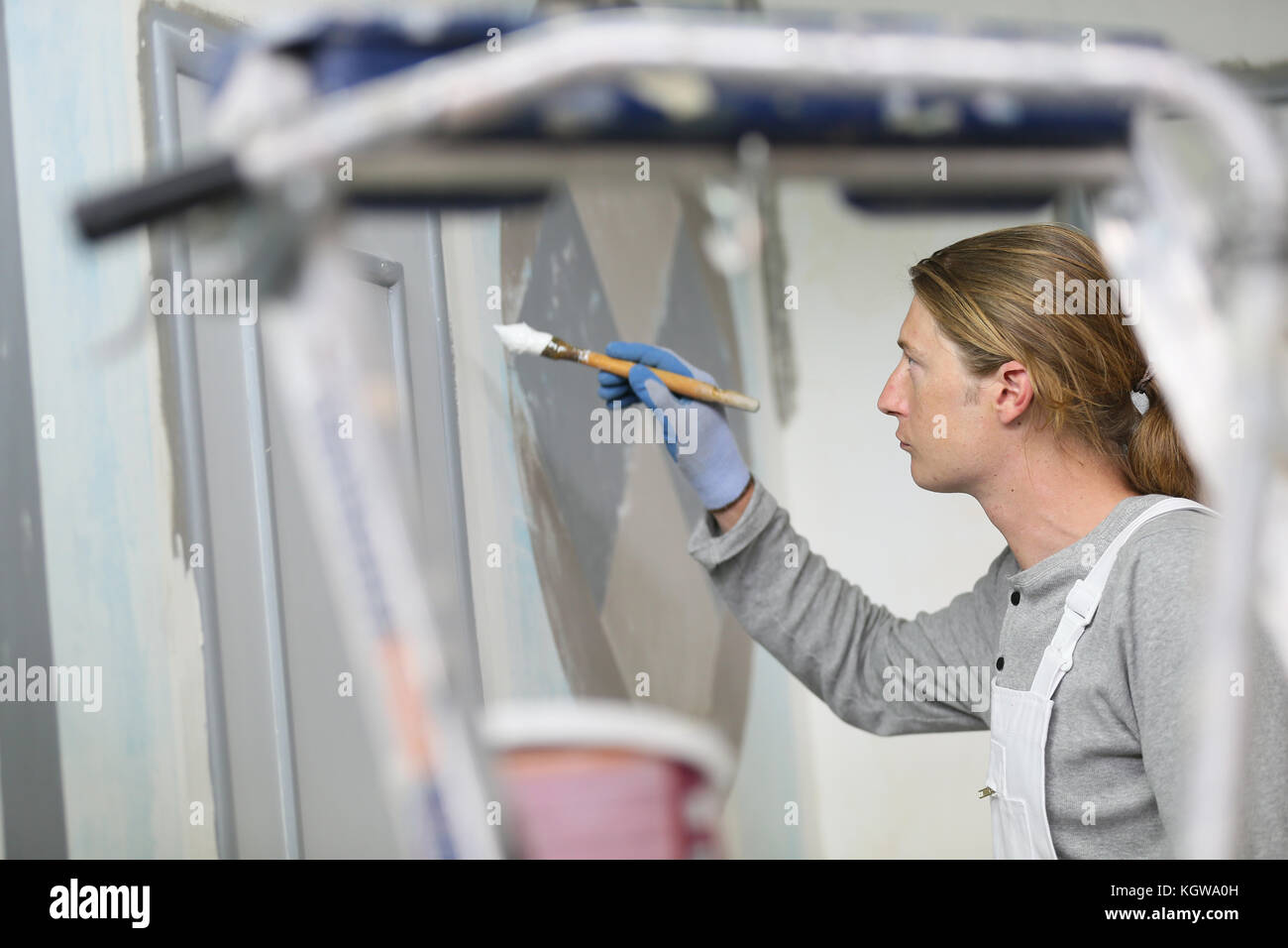 Professional painter painting room wall - Stock Image