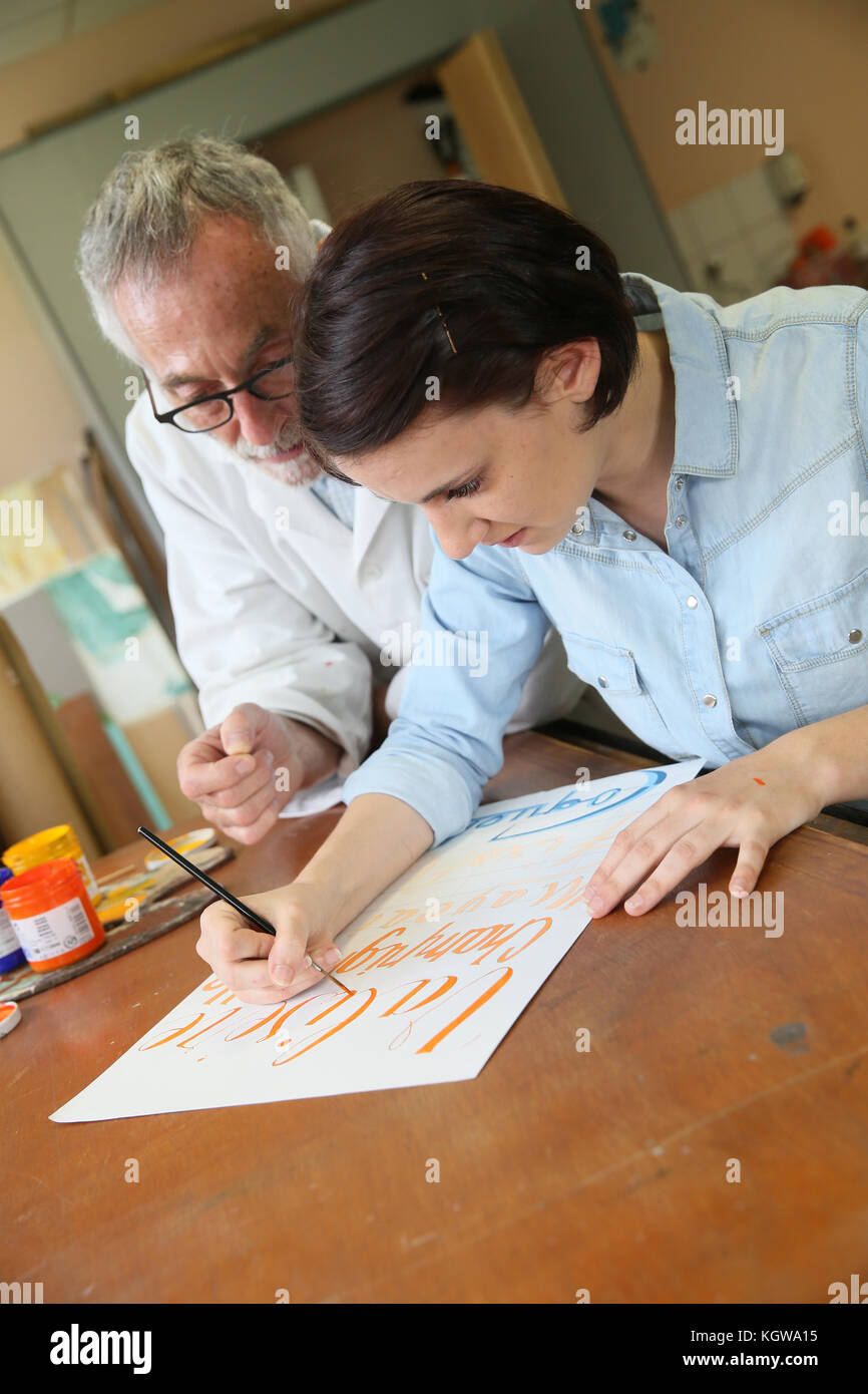 Young woman at school studying decorative painting - Stock Image