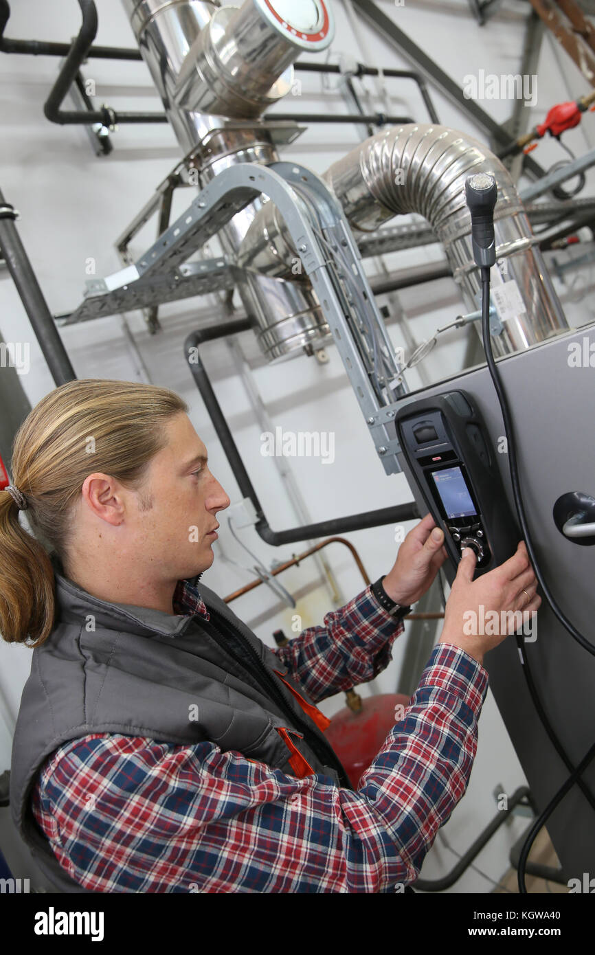 Technician checking heat pump intensity with electronic device - Stock Image