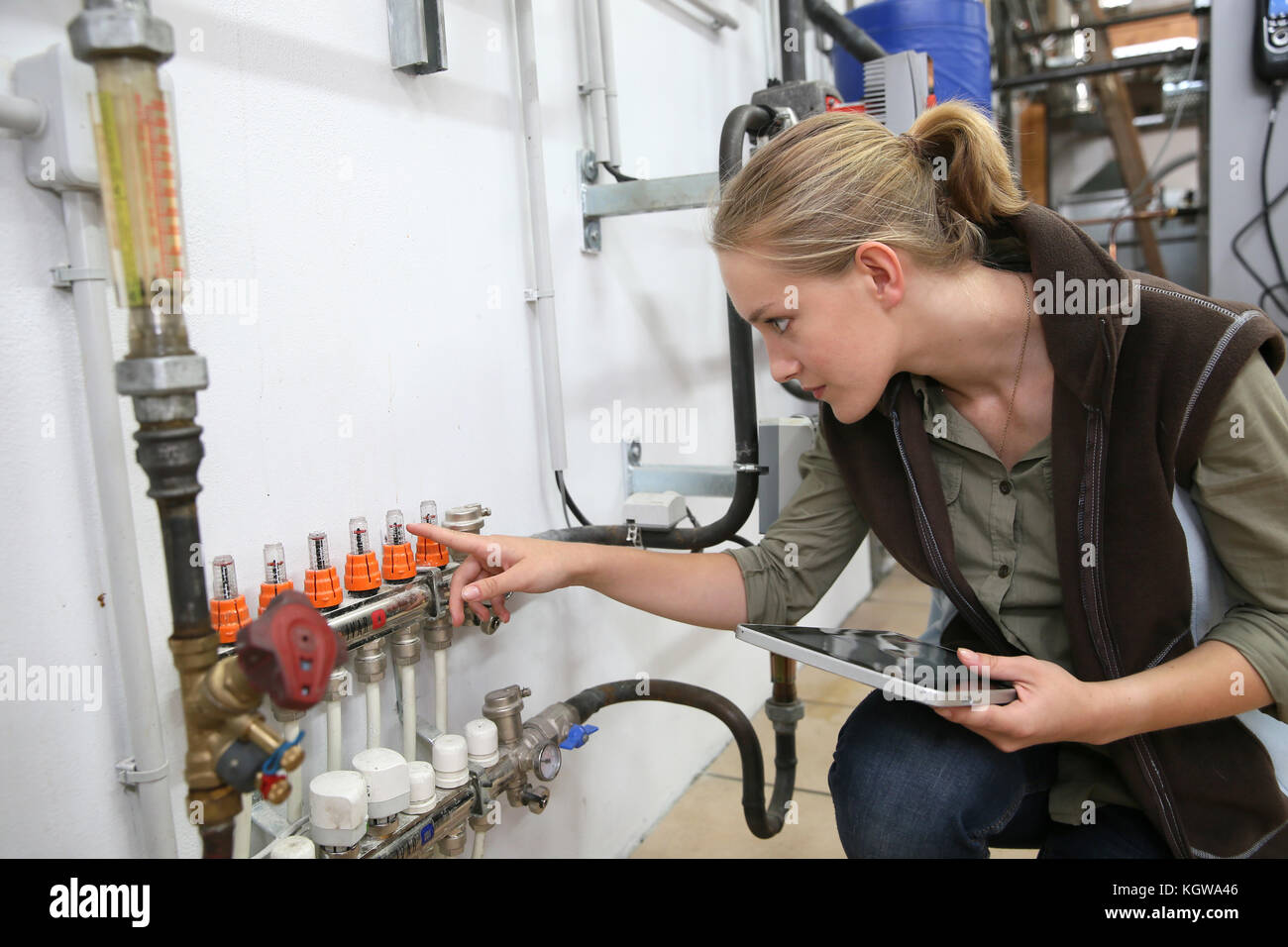 Young woman controlling water level in machinery - Stock Image