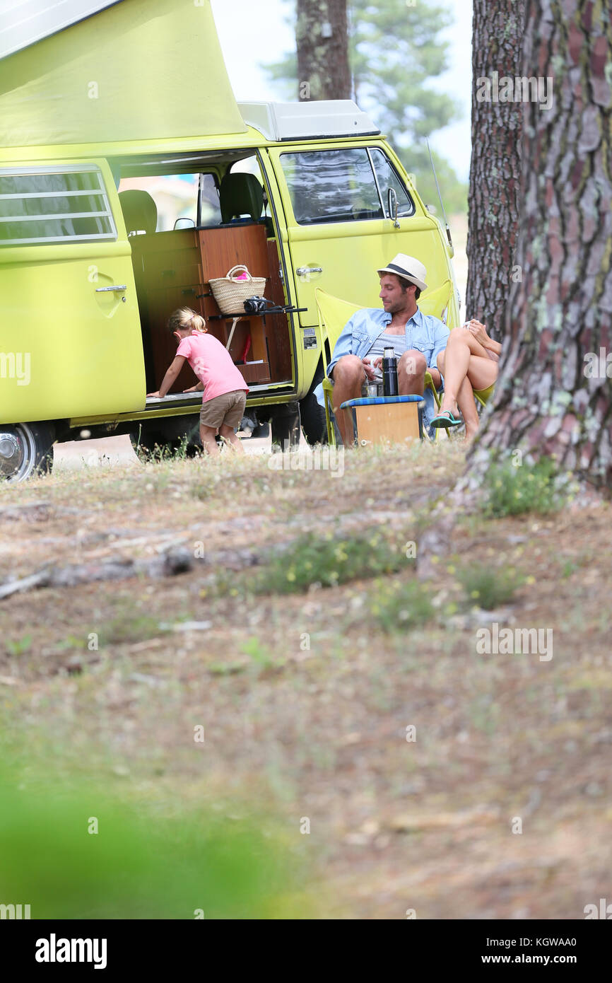 happy family relaxing by camper van in summer - Stock Image