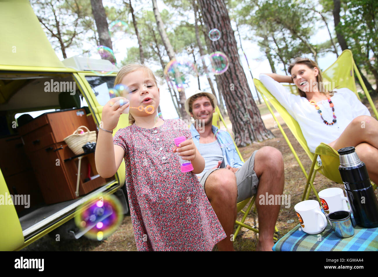 Little girl blowing soap bubbles, parents in background - Stock Image