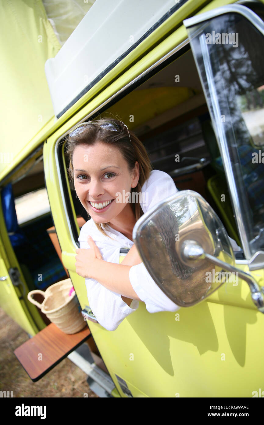 Portrait of cheerful woman sitting in vintage camper van - Stock Image