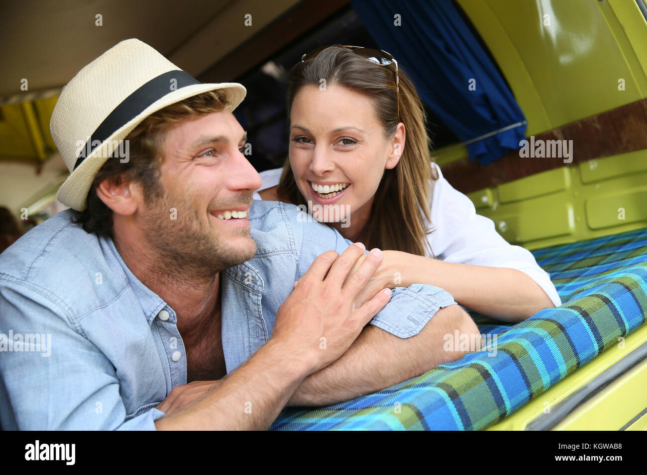 Cheerful young couple laying on a camper van - Stock Image