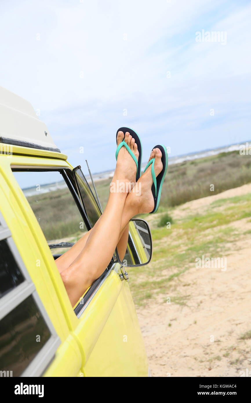 Closeup of woman's feet relaxing by camper van window - Stock Image
