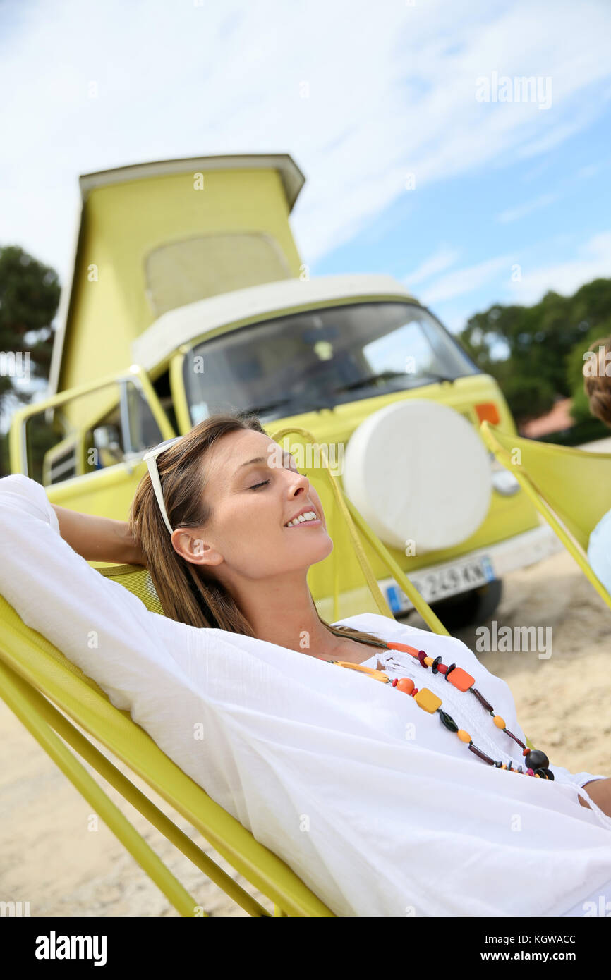 Cheerful woman relaxing in chair by camper van - Stock Image