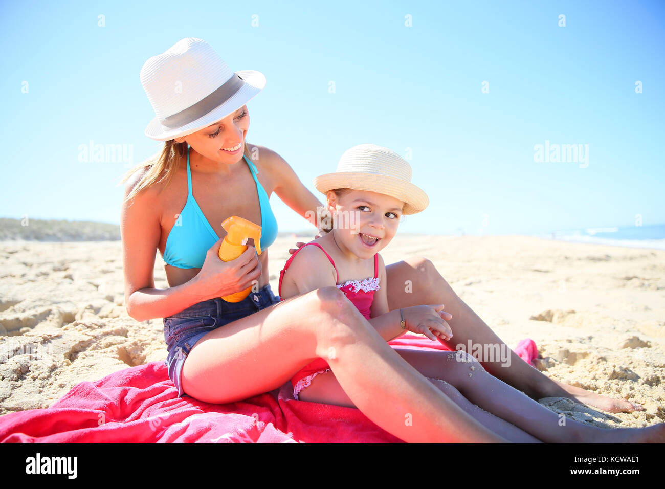 Woman applying sunscreen on daughter's body - Stock Image