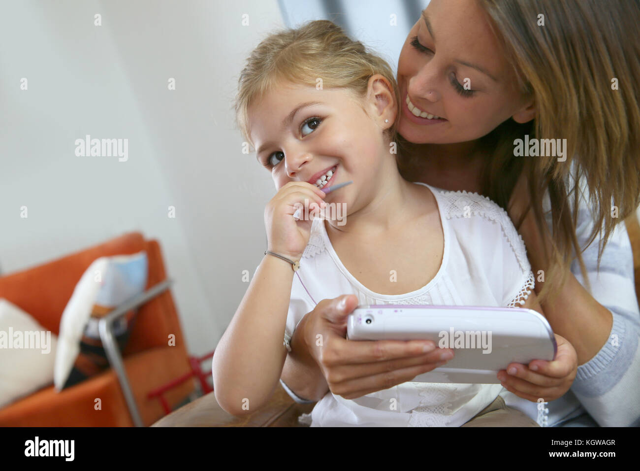 Mommy with little girl playing with video game player - Stock Image