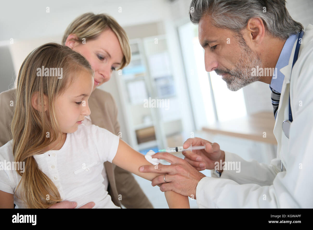 Young girl receiving vaccination in doctor's office - Stock Image