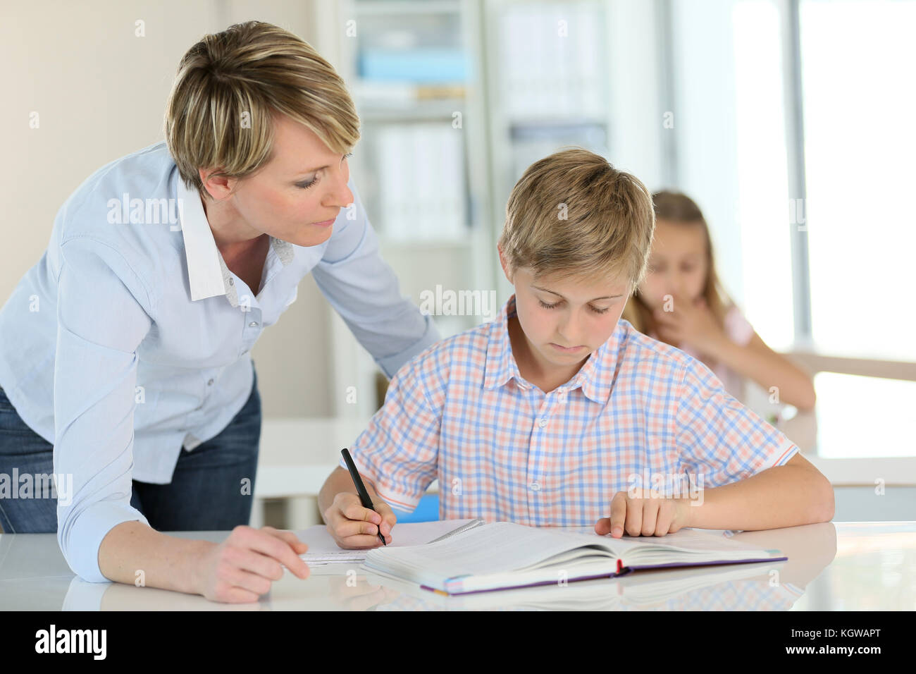 Teacher with schoolboy in classroom - Stock Image