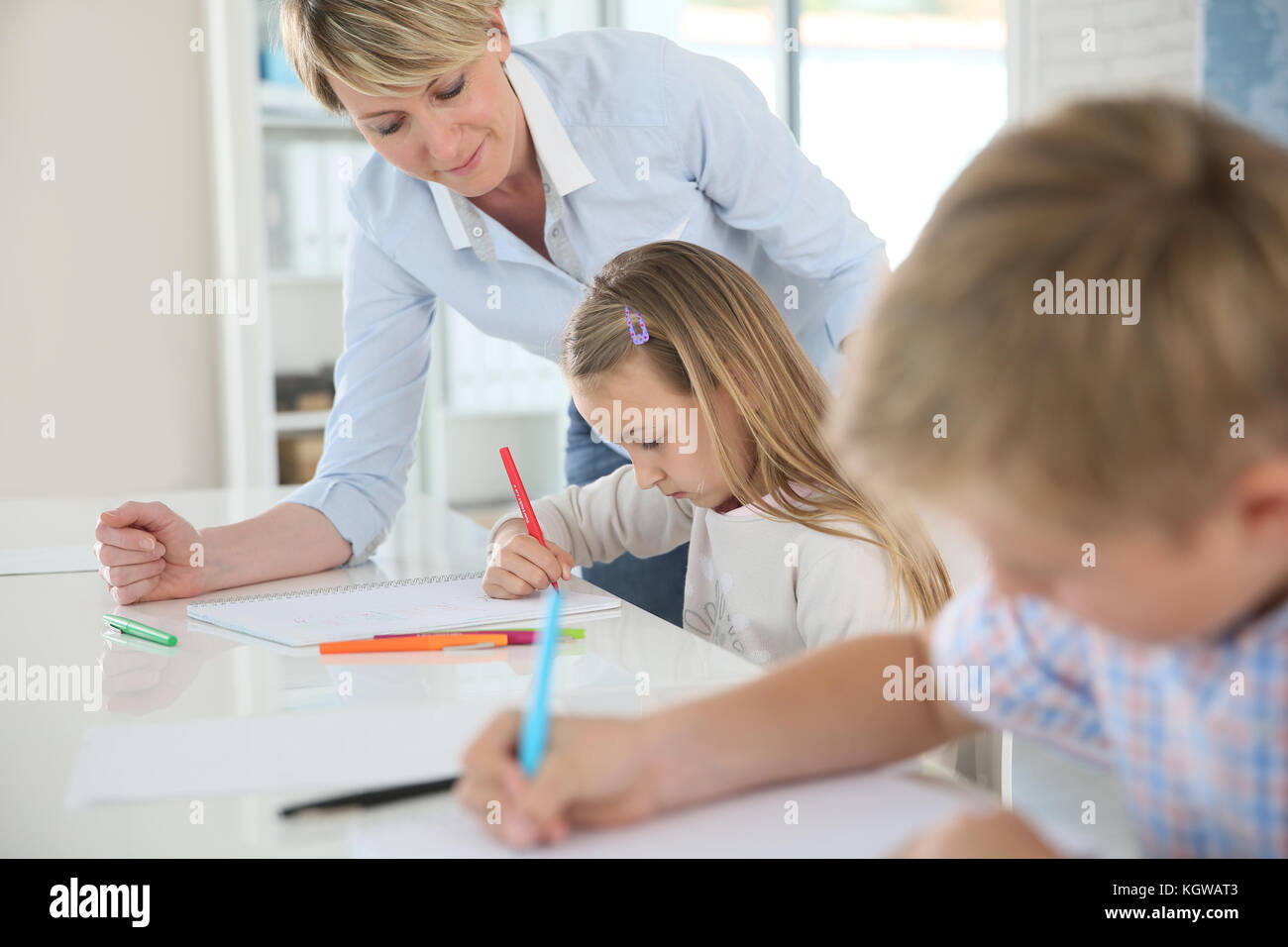 Teacher helping kids in classroom - Stock Image