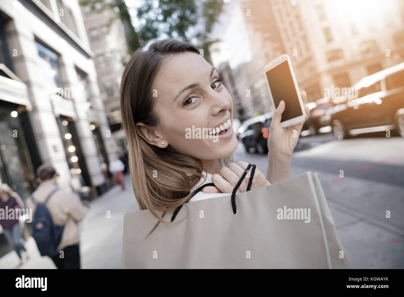 Cheerful girl shopping in Manhattan and talking on phone - Stock Image