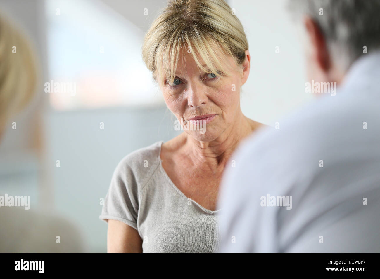 Senior woman attending group therapy - Stock Image