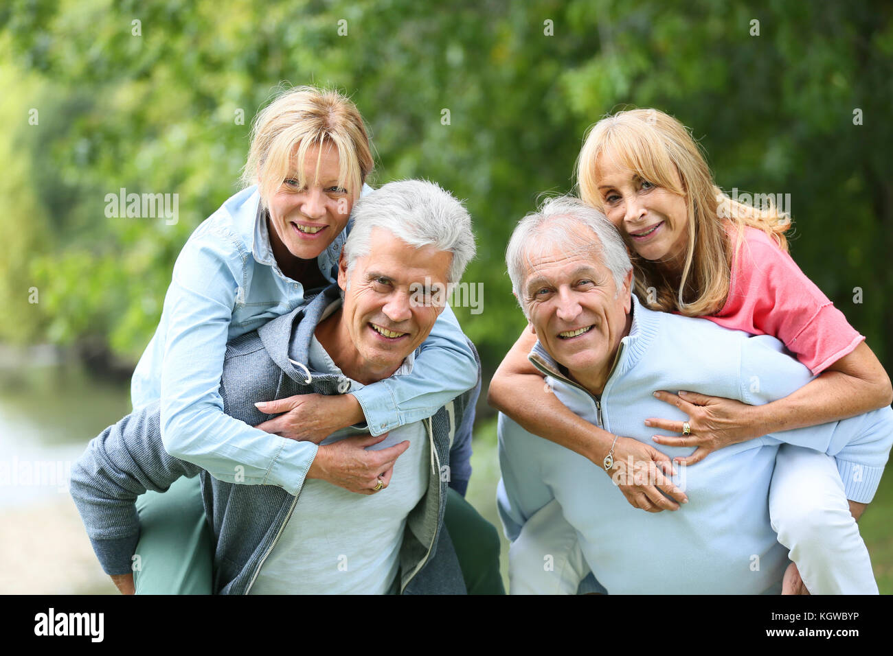 Senior men giving piggyback ride to senior women - Stock Image
