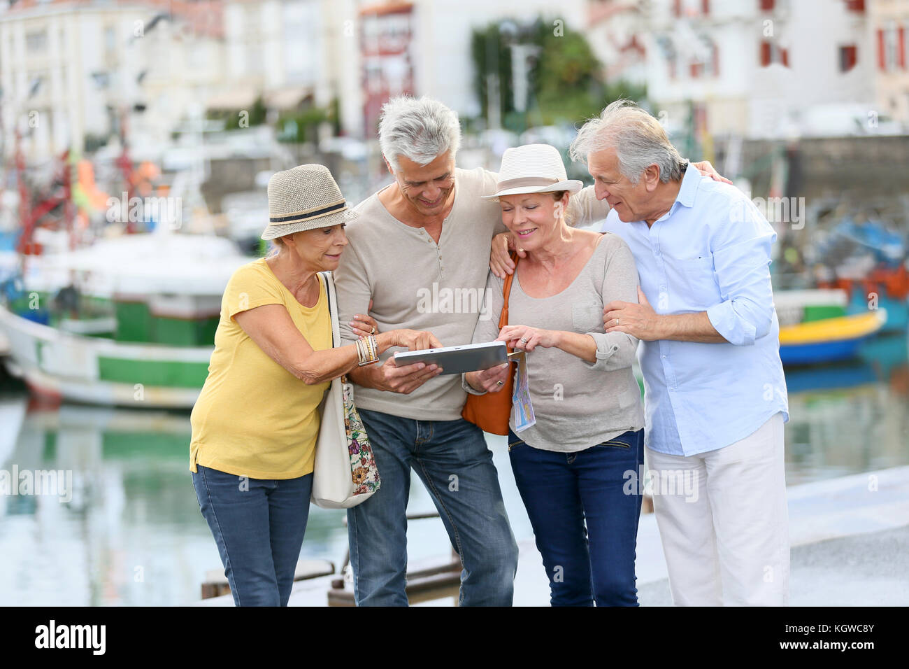 Senior couples looking at map on traveling journey - Stock Image