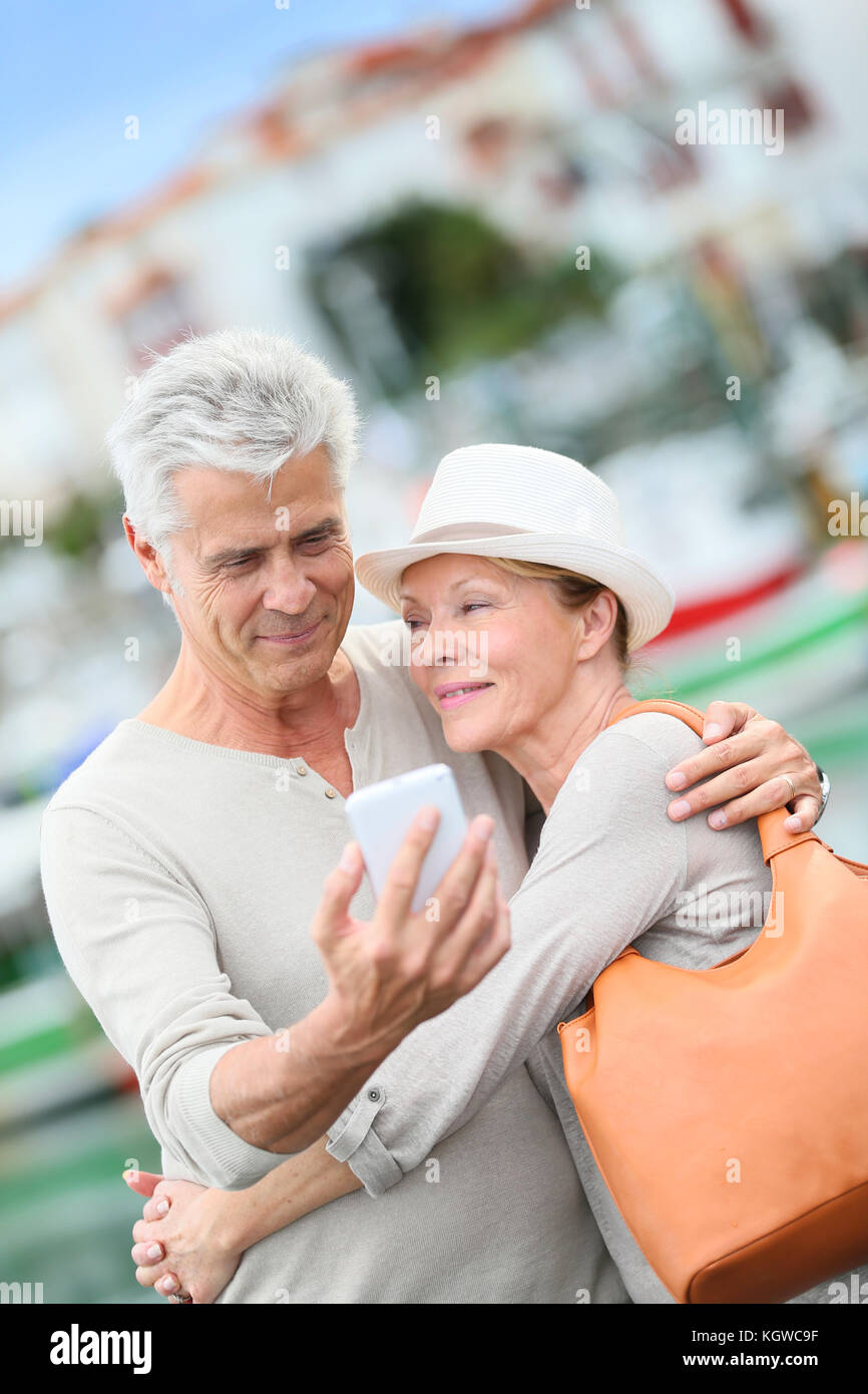 Senior couple of tourists taking picture with smartphone - Stock Image