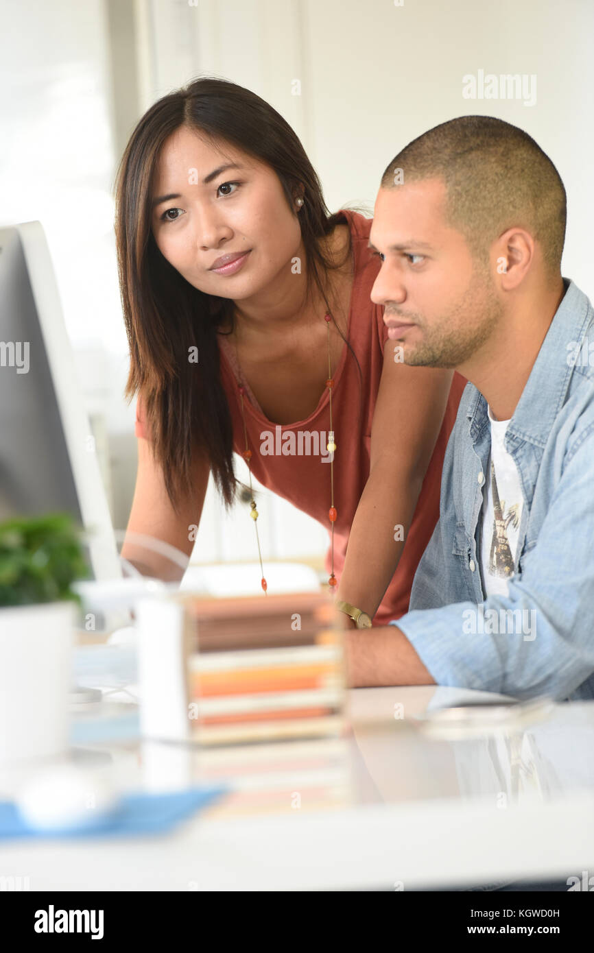 Business people in office working together on desktop - Stock Image