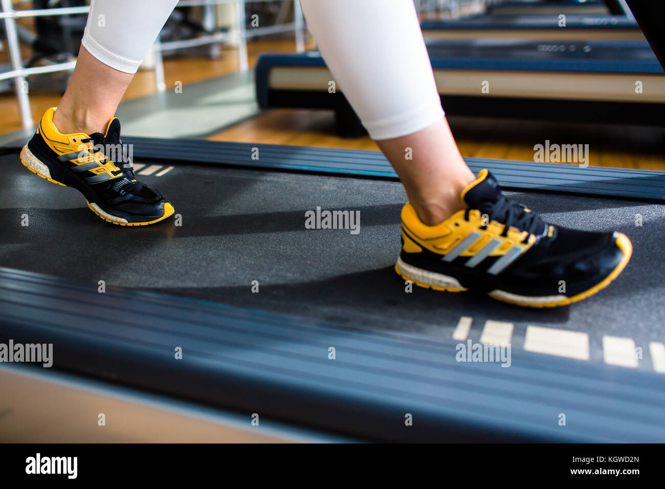 Human feet on threadmill moving track during workout in gym - Stock Image