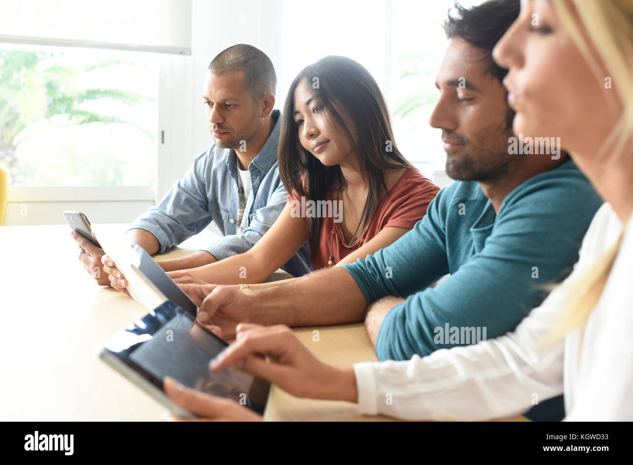 Start-up business people meeting with tablets and smartphones - Stock Image