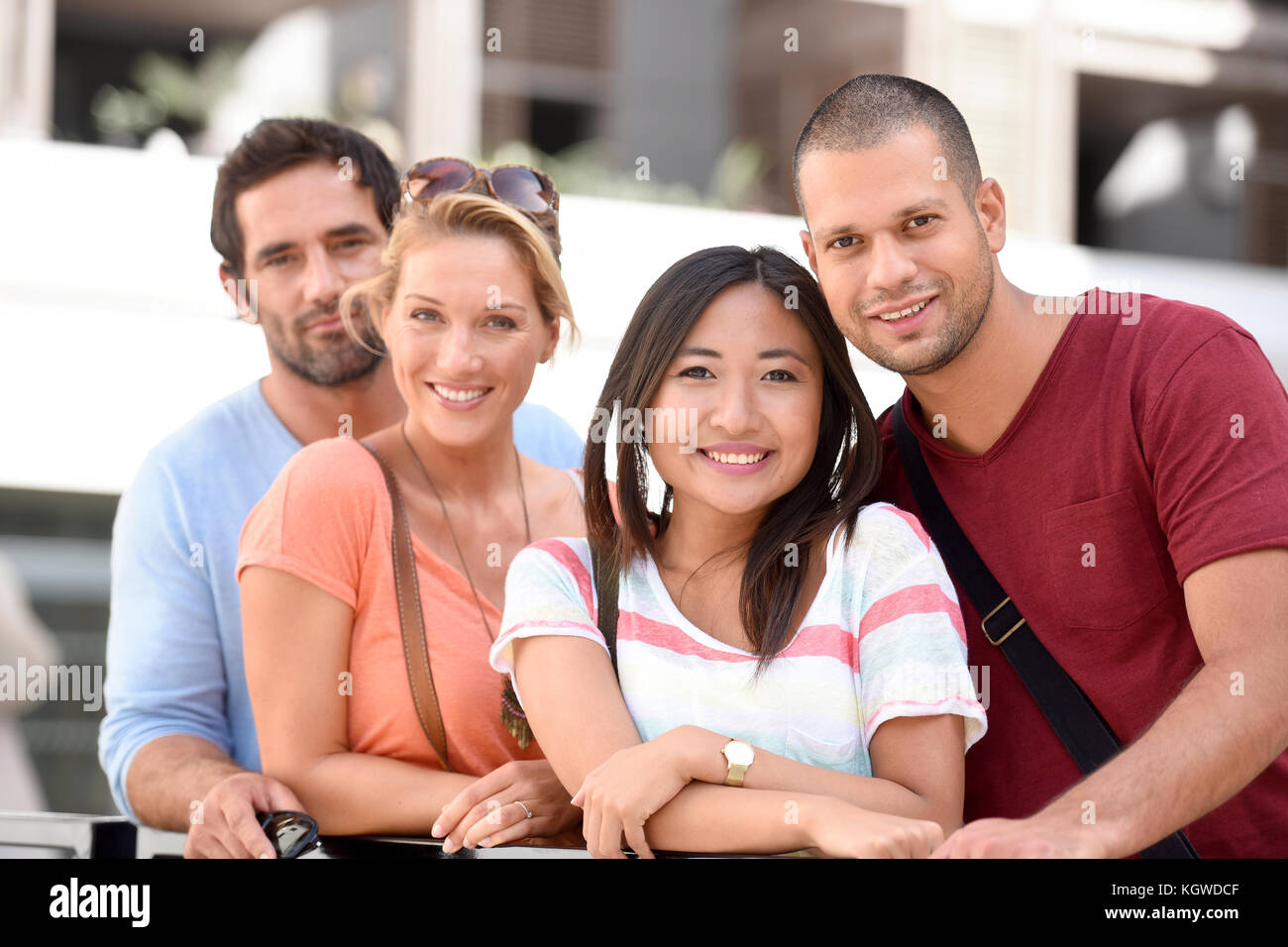 Group of young couples standing by building of apartments Stock Photo