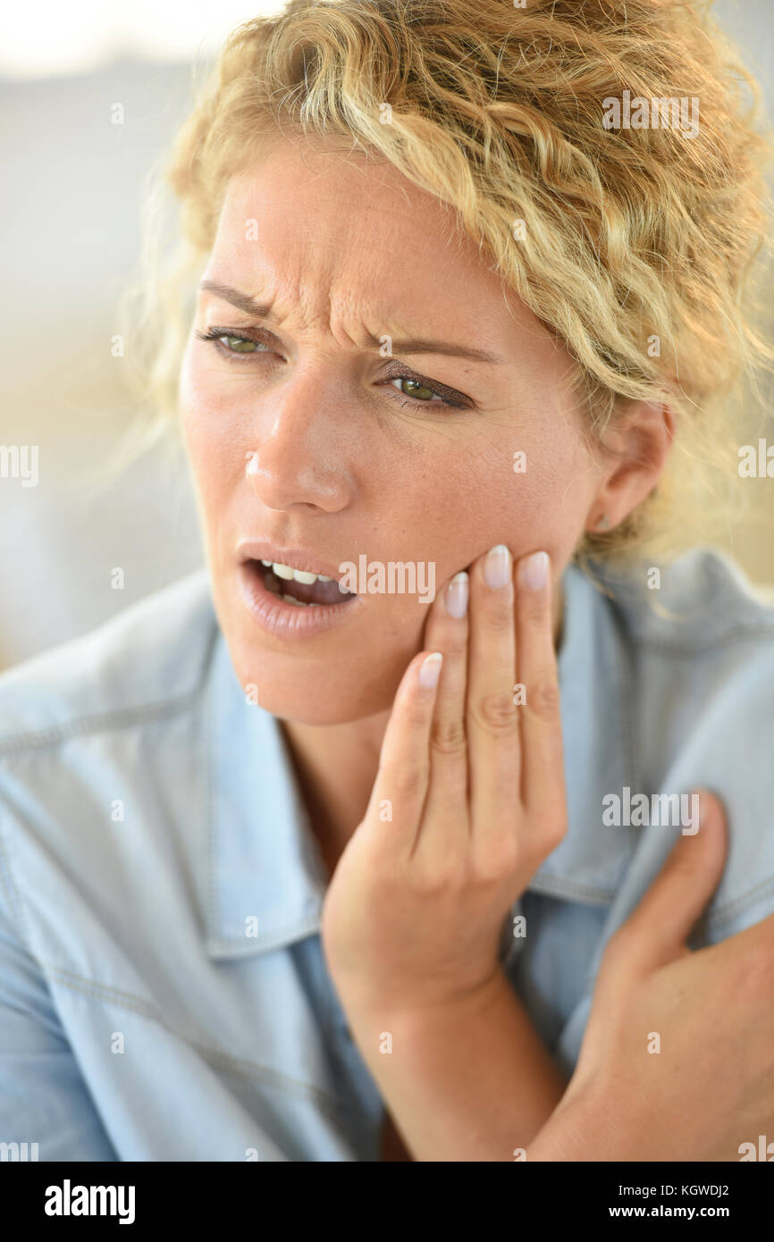 Middle-aged woman suffering toothache - Stock Image