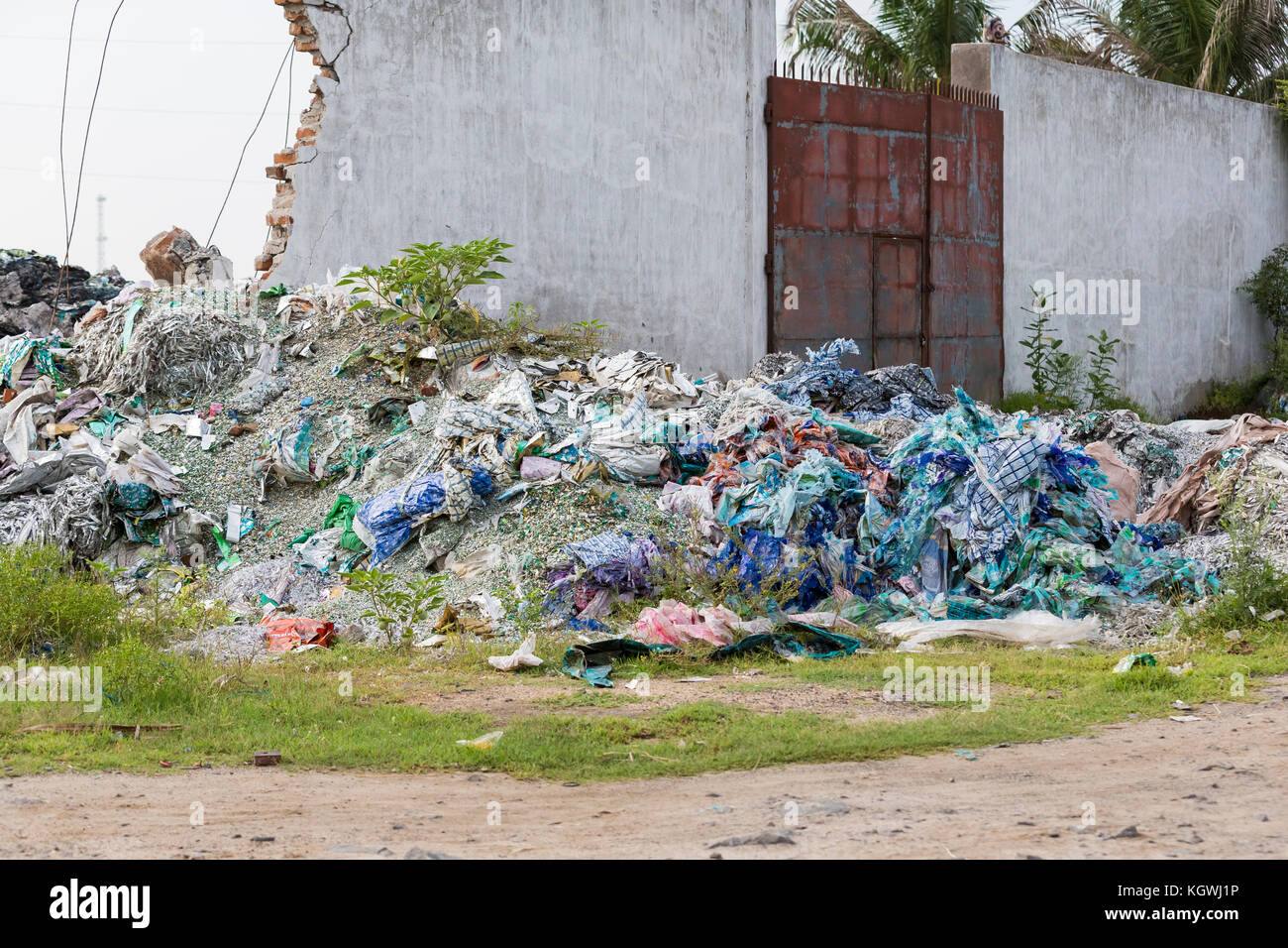 waste plastic bottles and other types of plastic waste near the house in the street city, India, Tamil Nadu - Stock Image